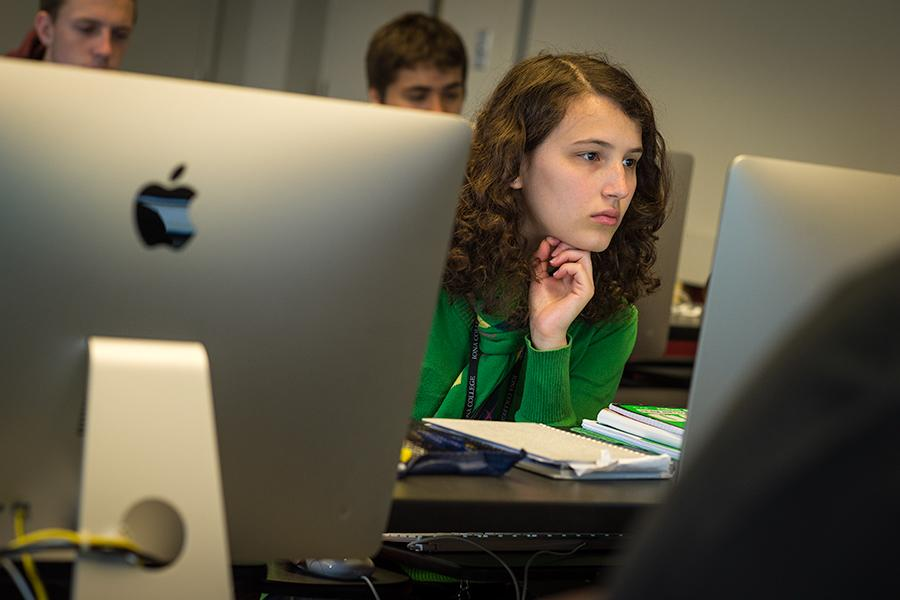 A student sits between two iMacs and works in the computer lab.