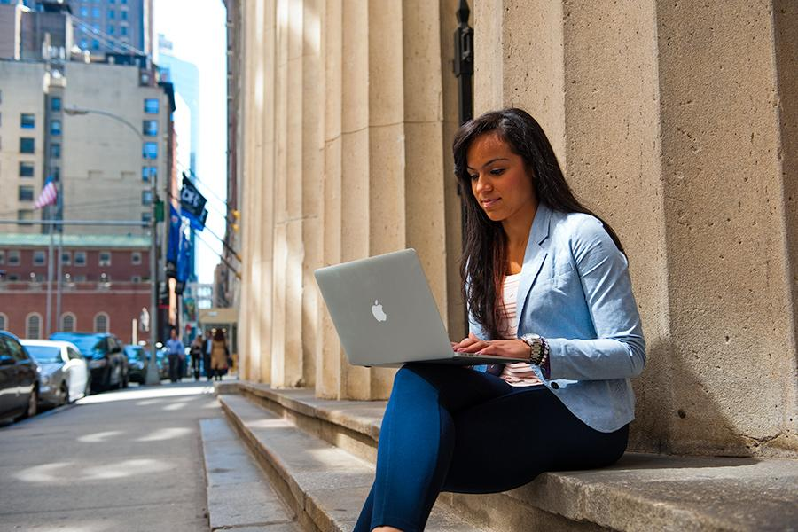 A student sits in New York City and works on her laptop.