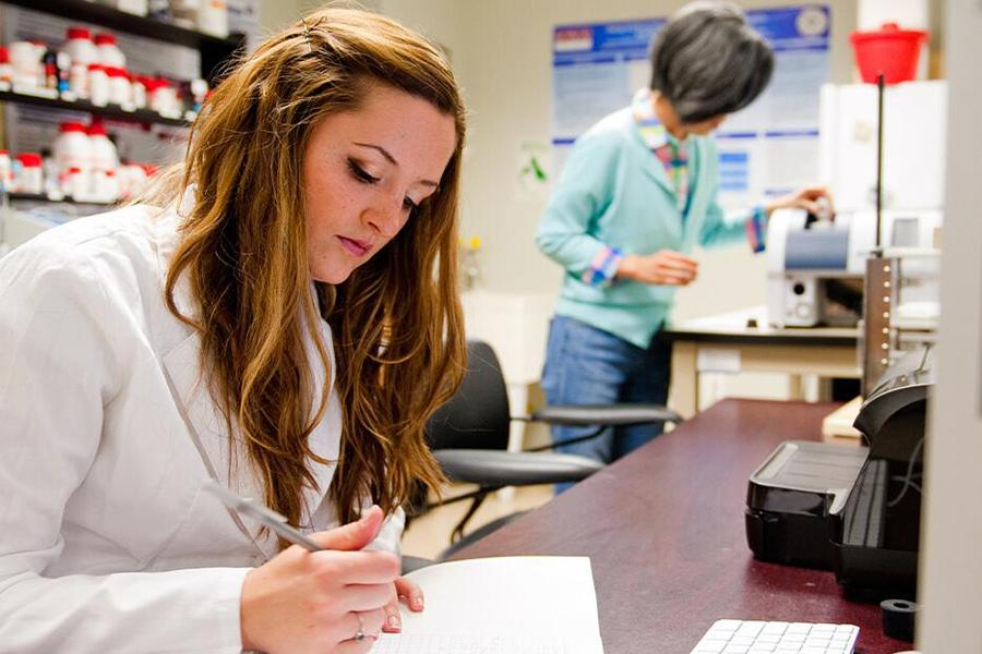A student in a white lab coat writes something down while Sunghee Lee works in the background.