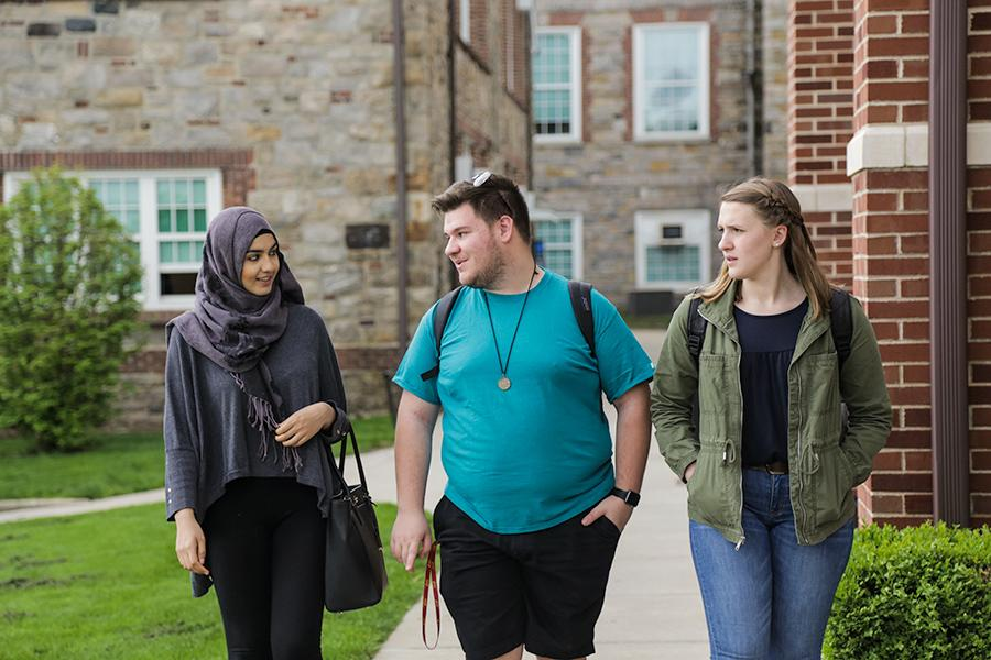 Three Diversity and Social Welfare students walk side by side next to East Hall.