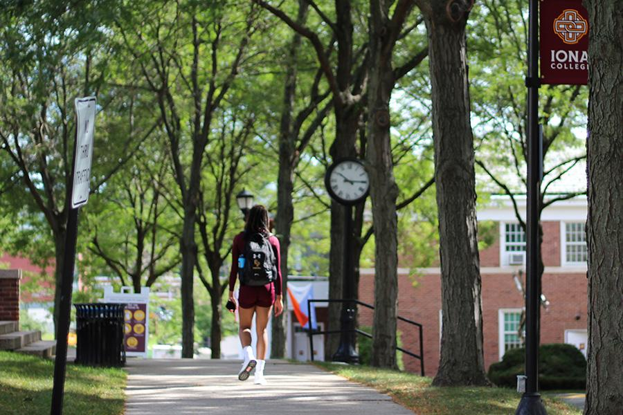 A male student walks down the main pathway of campus.