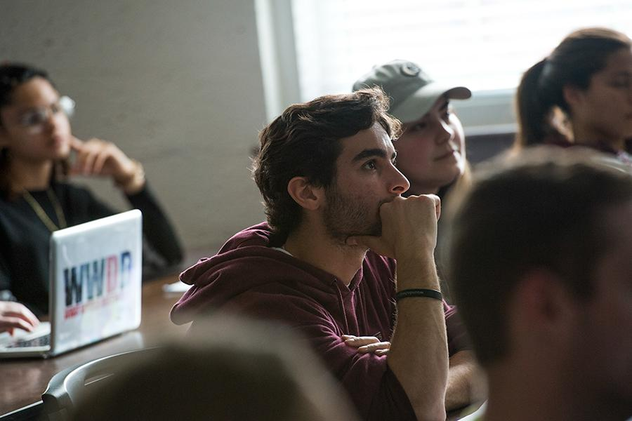 A student listens very intently during a lecture with his hand by his face.