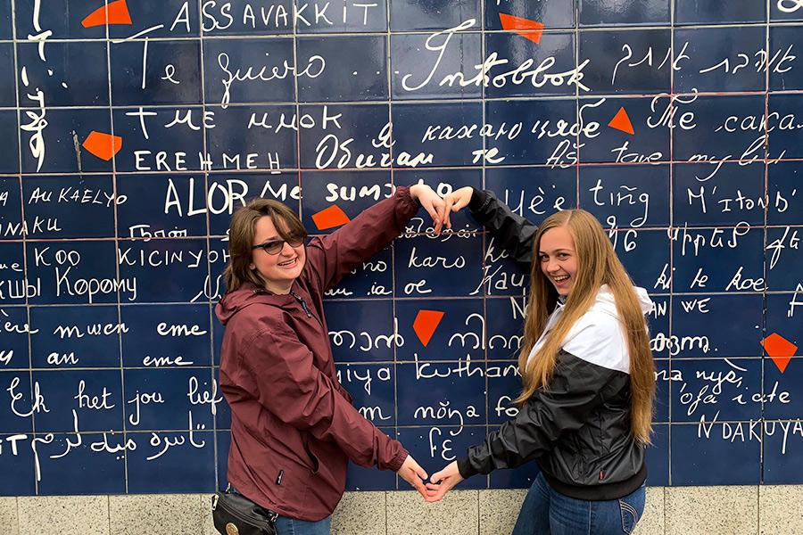 Two Iona students pose with their arms in a heart during the study abroad program in France.