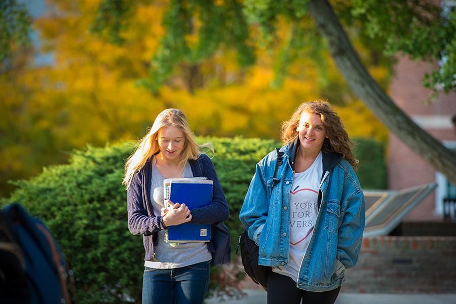 Two students walk on campus during early autumn in golden sunlight. One wears a jean jacket and the other carries books.
