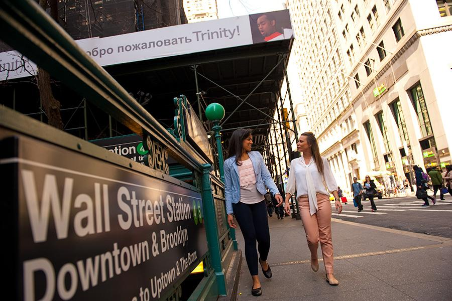Two students walk on the street in New York City near the Wall Street subway.