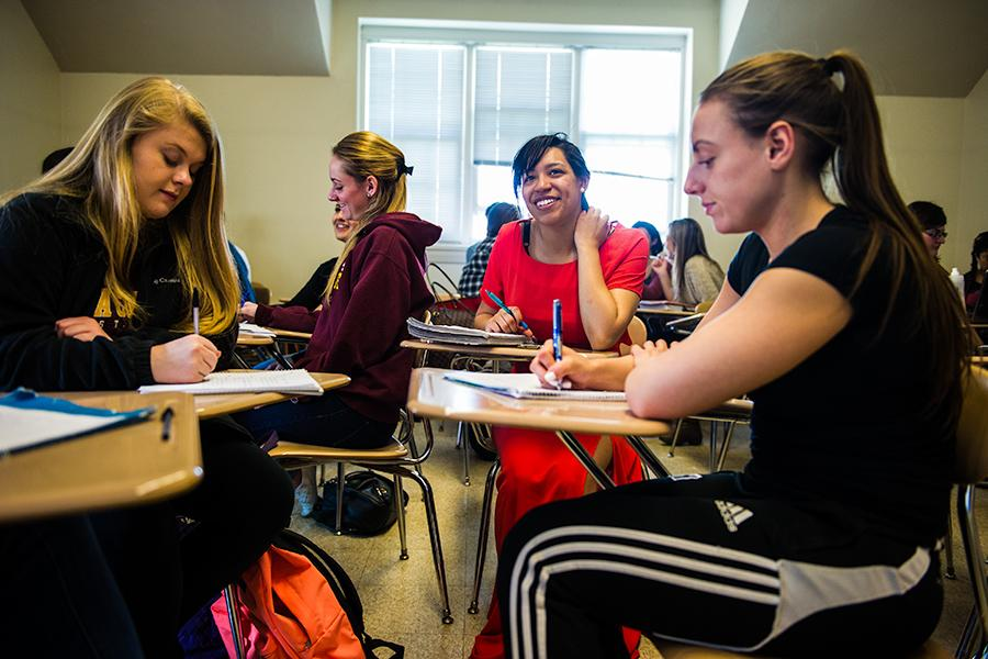 Four female students sit at desks in a classroom writing notes for their psychology class.