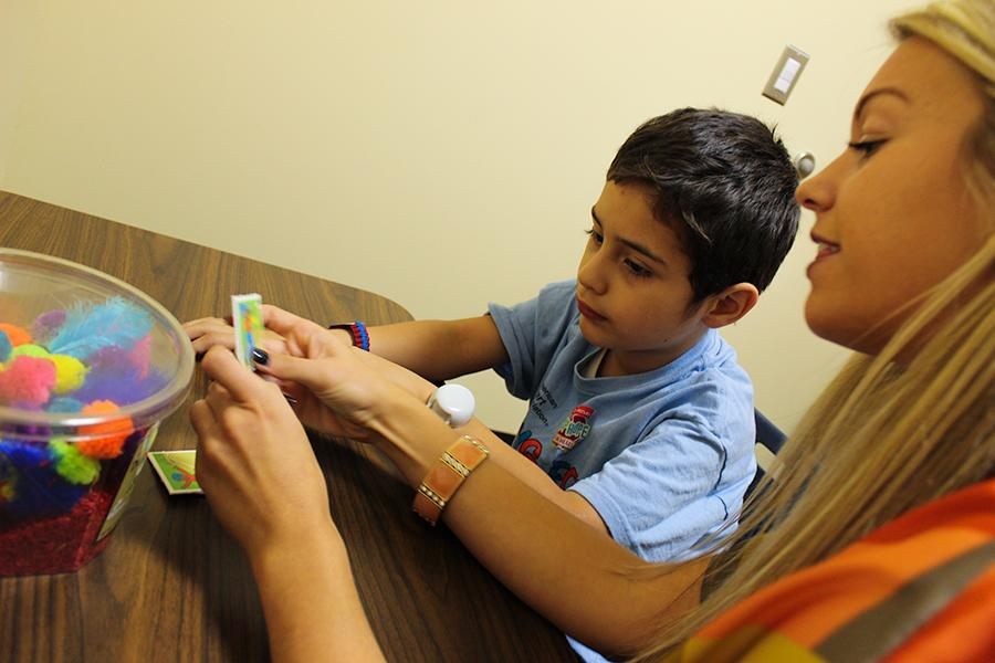 A female student works with a child client in the campus therapy center.