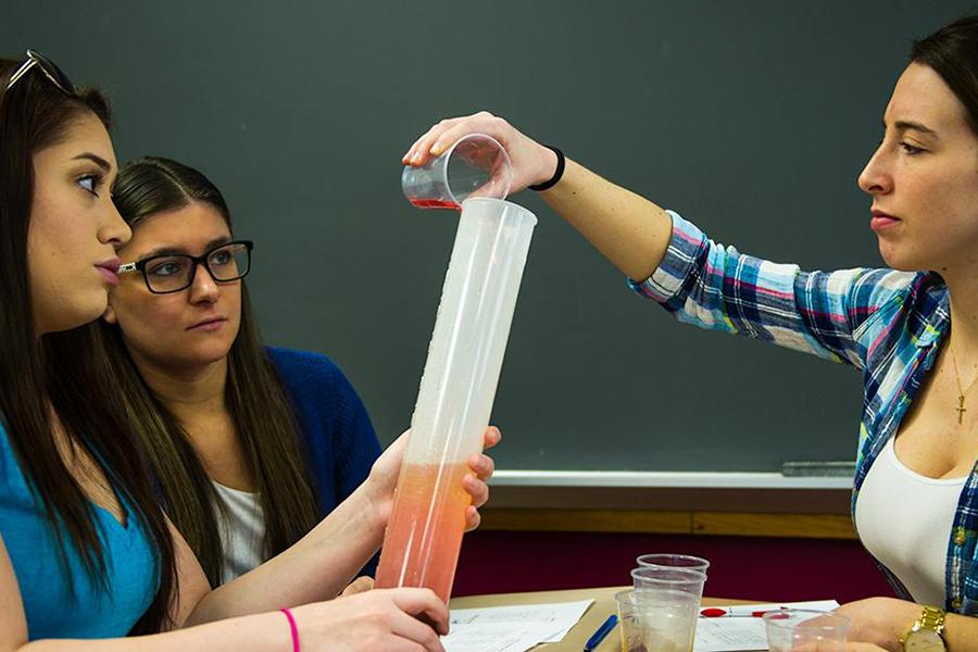 Three students sit at a table in chemistry class. One pours liquid into a cylinder and another holds the cylinder.