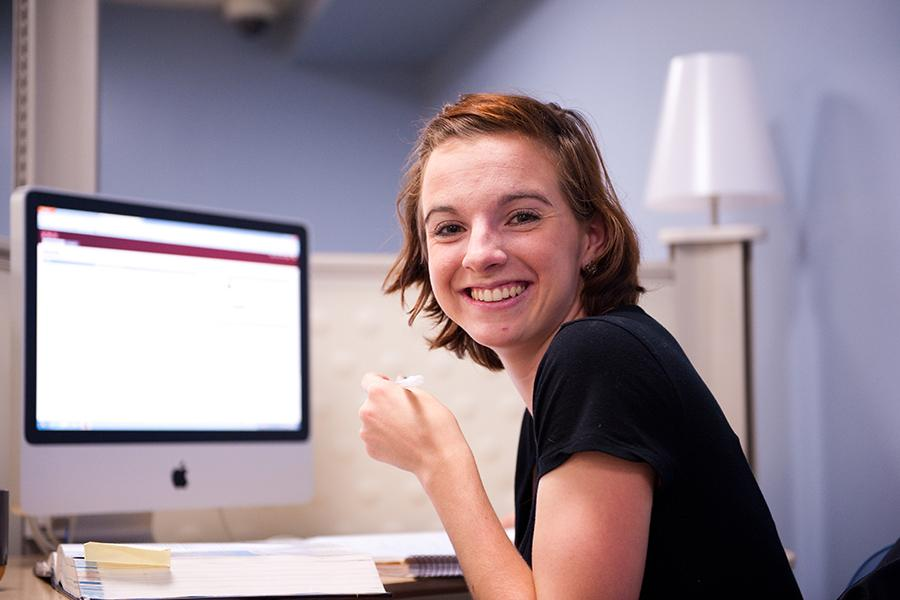 A student logs in to her MyIona account and turns around and smiles.