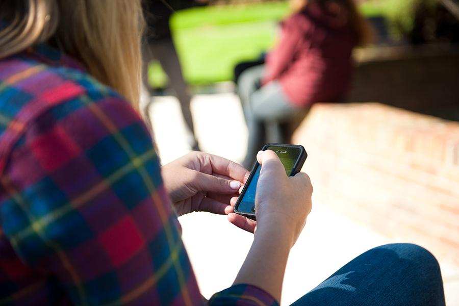A person in a flannel shirt sits on a bench and uses an iPhone.