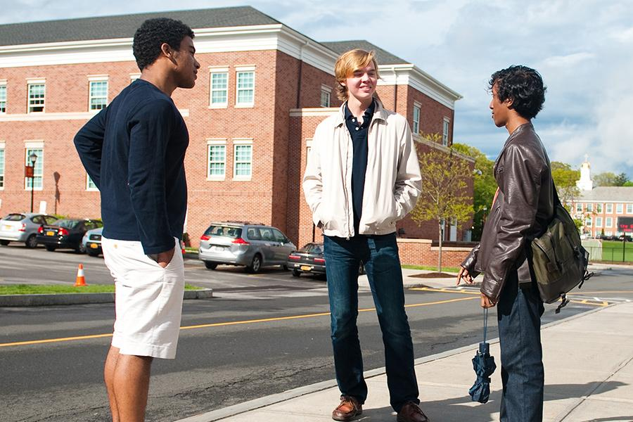 Three students stand on the sidewalk outside of Spellman and talk.