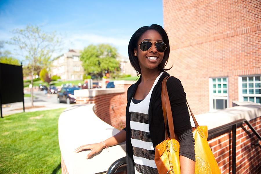 A student stands outside of the Starbucks on campus. She wears sunglasses and smiles.
