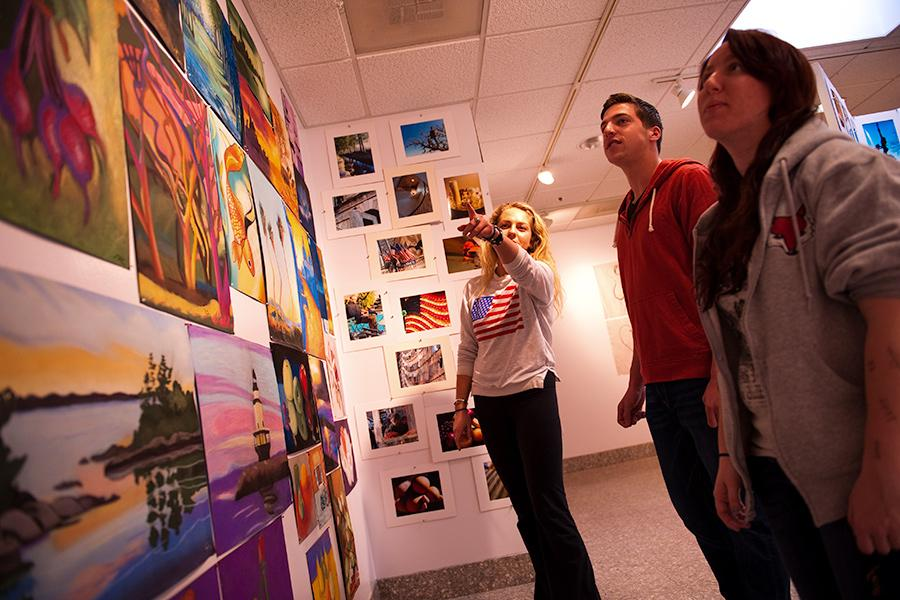 An arts leadership student shows off paintings to two other students in an art gallery.