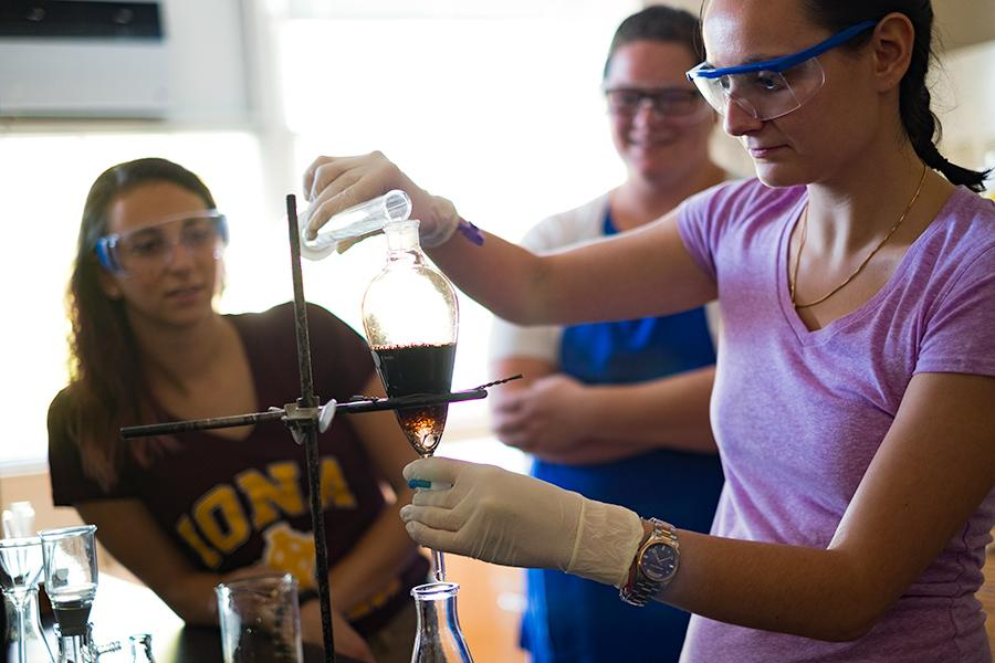 Three students are working in a biochemisty lab while wearing goggles