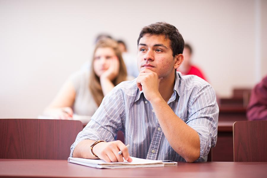 A student rests his chin in his hand during a lecture for an psychology class.