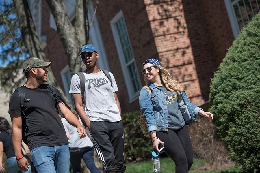 Two male students and one female student walk on campus and smile and talk. They are all stylish and artsy.