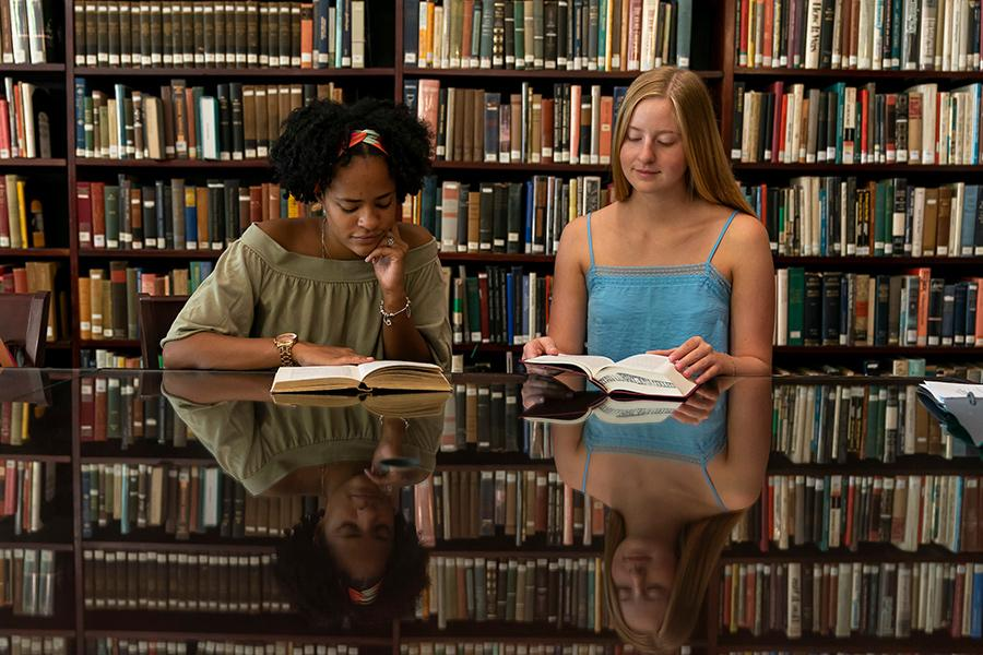 Two students sit in the library to read books for a history class.
