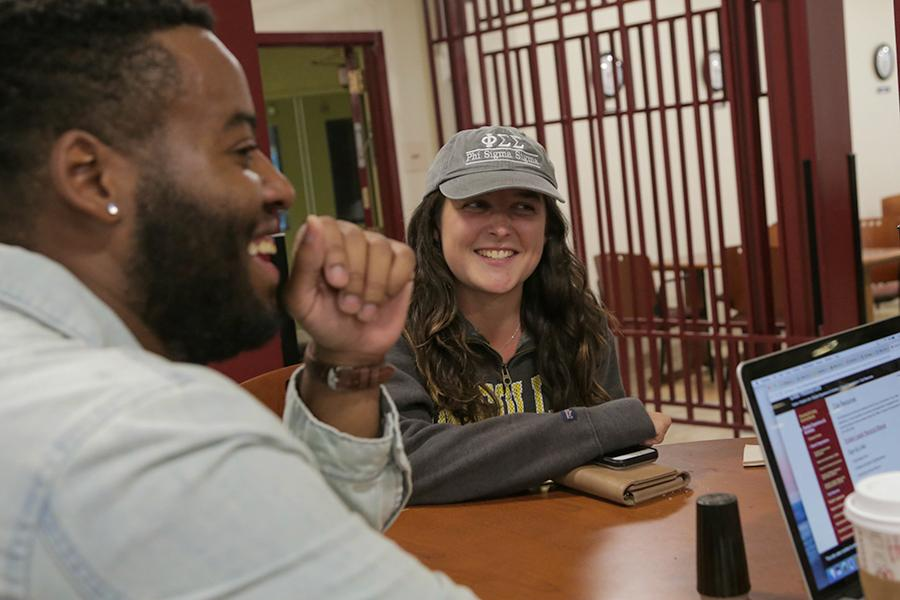 A student with a sorority cap smiles and talks to a student with a beard who smiles and laughs.