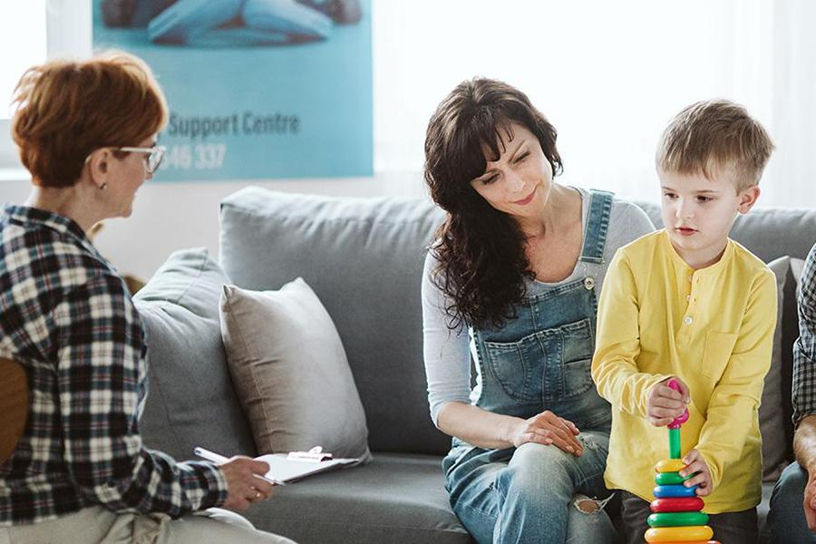 A therapist works with a family including the mother and young son.