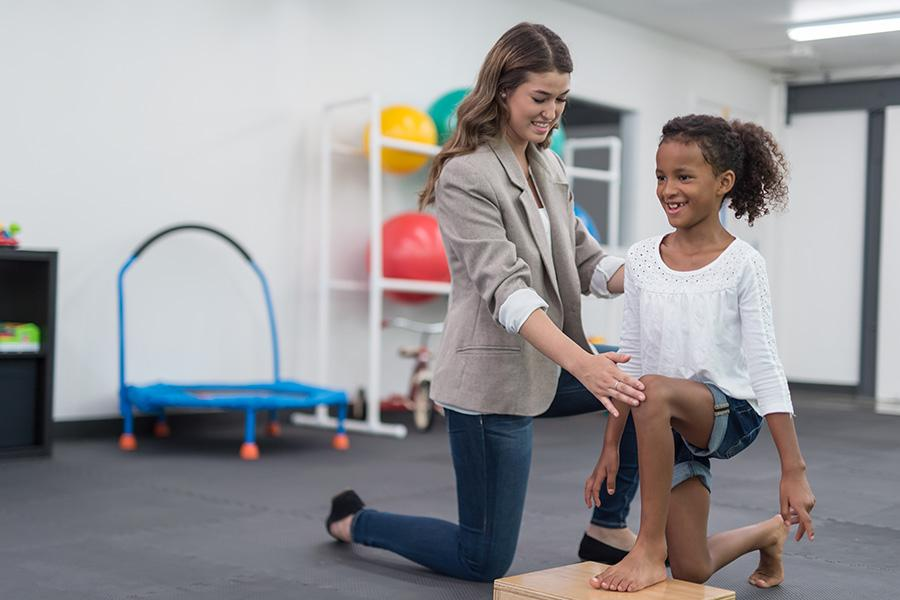 A female occupational therapist assists a young female child in a session.