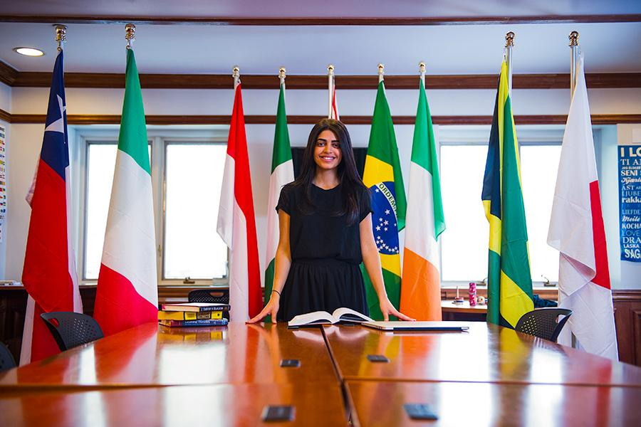 An international business student stands in front of a row of flags from several different countries.