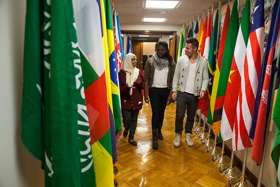 Three international studies students walks down a hallway lined with flags from different countries.