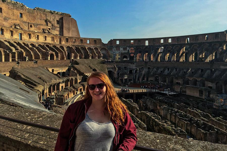 A student stands in the Colosseum in Rome, Italy.