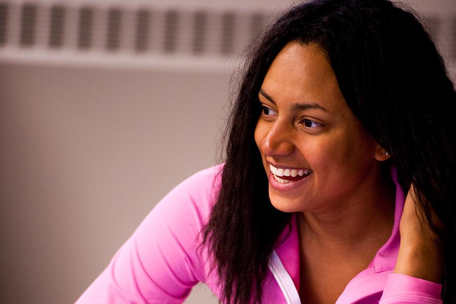 A student in a pink hoodie smiles brightly in a marketing class.