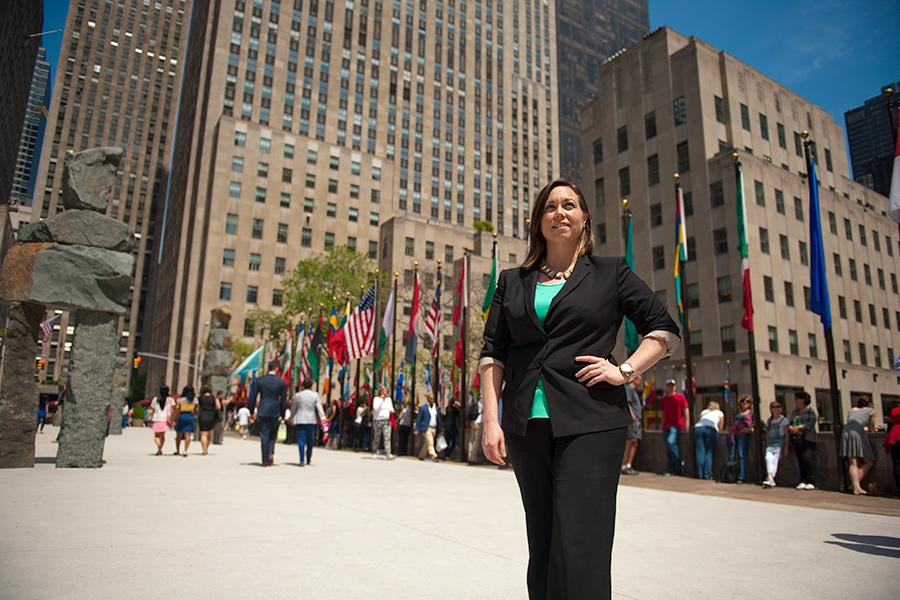 A student visits Rockafeller center in New York City and stands near the flags of the world.
