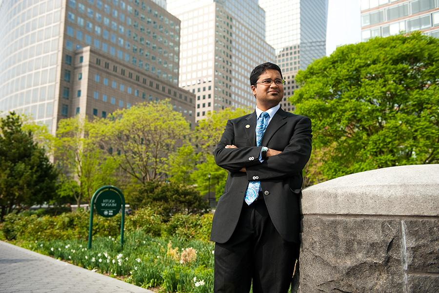 A student in a suit stands confidently in a park in New York City with his arms crossed.