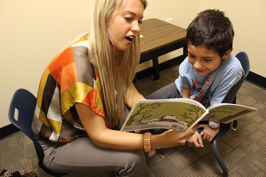 A speech therapist reads a book to a young client.