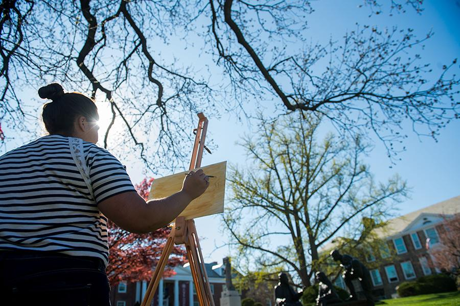 A female student stands at an easel painting in the campus quad.