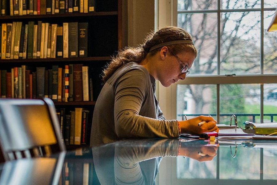 A student sits at a table in the library by the window and writes with pen and paper.