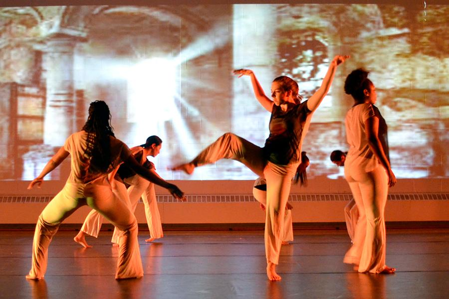 A dance ensemble performs with a video screening in the background.