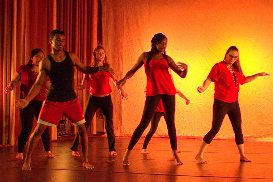 A group of students perform in a dance ensemble with orange lighting.