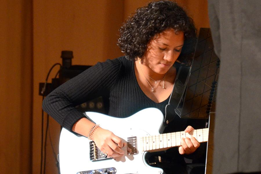 A student plays guitar in the band.