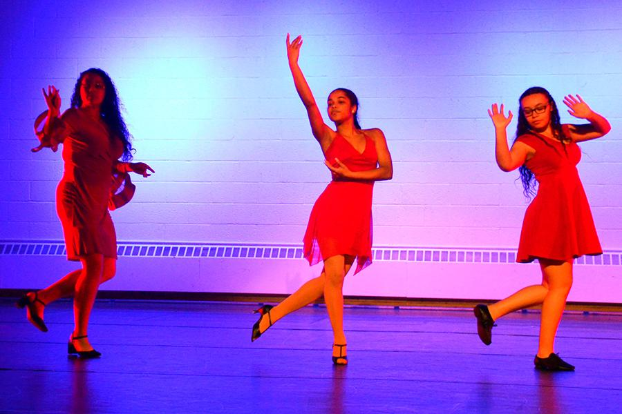 Three dancers perform in red dresses.