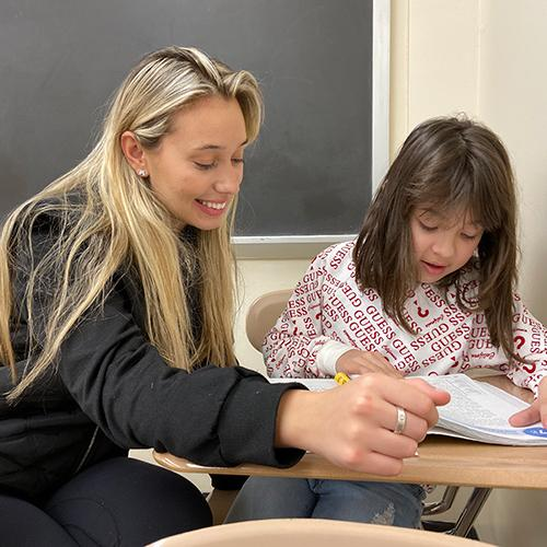 Amanta Krasniqi '22, an adolescent education major at Iona College, reads with Valentina Oroco, a third grader at William B. Ward Elementary School in New Rochelle.
