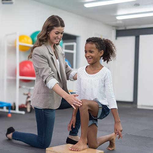 An occupational therapist works with an adolescent girl on her knee movement.