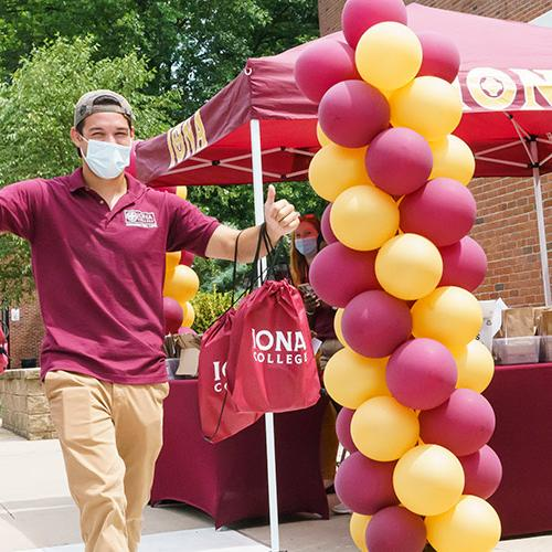 An orientation leader carries tote bags and swag near a table with balloons to welcome new Iona students.
