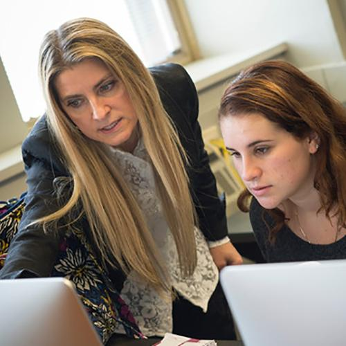 Paolina Centonze helps a student at a computer.