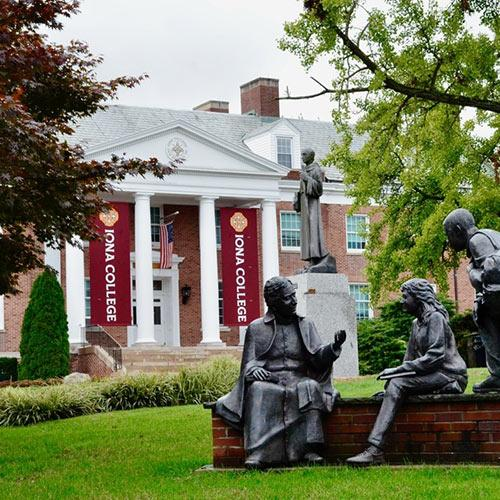 "The ""To Teach"" statue in the Iona campus quad with McSpedon Hall in the background"
