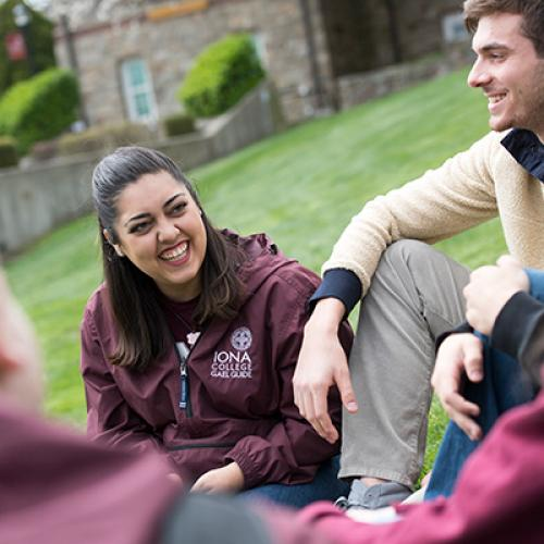 Students sit and talk on the east lawn. One student wears a Gael Guides jacket.
