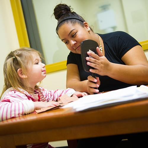 A student works with a young girl at the speech clinic.