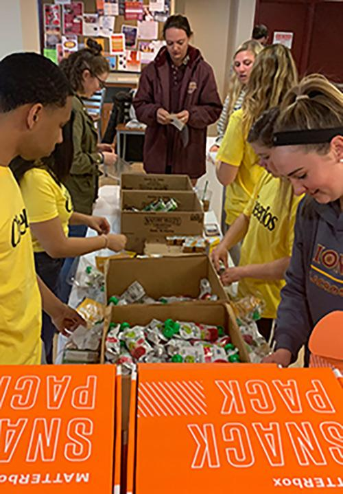 Students work to fill boxes with food for One Million Acts of Good.