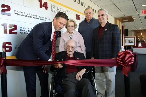 Matt Glovaski, Mary Jane Arrigoni, Jim Hynes and President Carey stand with Mr. Arrigoni as he cuts the ribbon.
