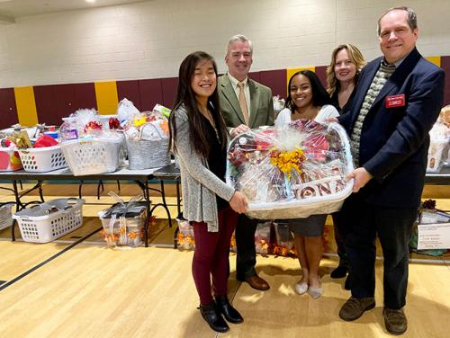 Faith Krefft, President Carey, Tamia Reyes, Noreen Carey and Carl Procario-Foley hold a basket at the 2019 Thanksgiving Baskets event.