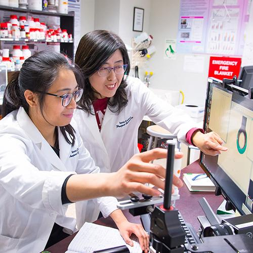 Sunghee Lee works with a student in her lab.