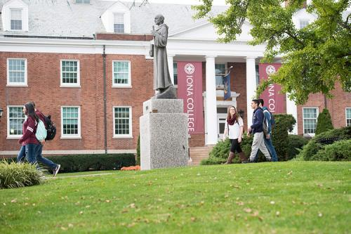 Iona students walk past the Columba statue in front of McSpedon Hall.
