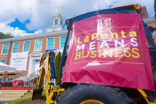 A backhoe with a tarp that reads LaPenta Means Business at the groundbreaking ceremony.